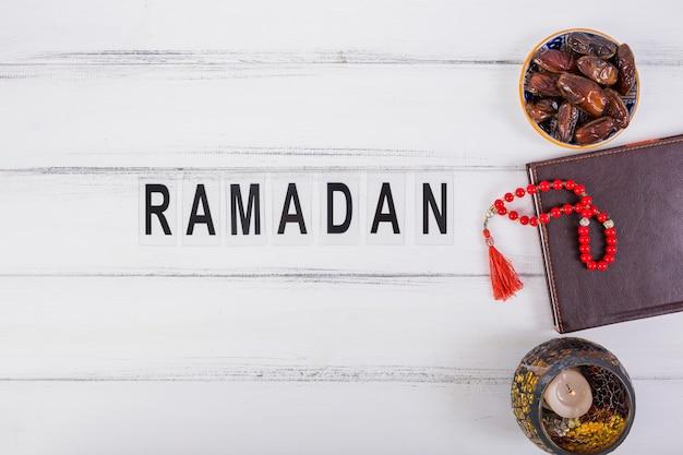 Texto de ramadán con cuenco de dátiles jugosos; diario y cuentas rojas de oración en mesa blanca
