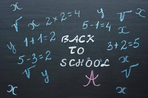 Texto de regreso a la escuela y ejemplos matemáticos en pizarra negra.
