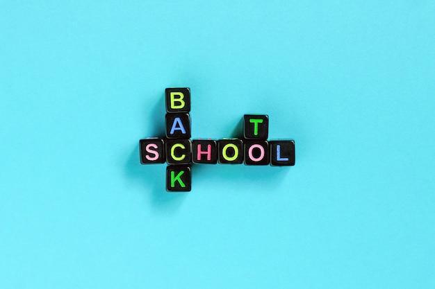Texto de regreso a la escuela de letras coloridas en cubos negros en forma de crucigrama