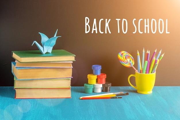 Texto de regreso a la escuela con libros, papelería en taza amarilla, pintura aguada y grulla de origami