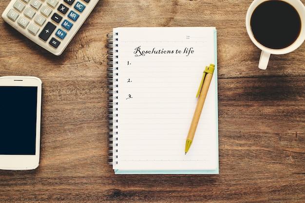 Texto de las resoluciones a la vida en nota de libro con una taza de café, pluma
