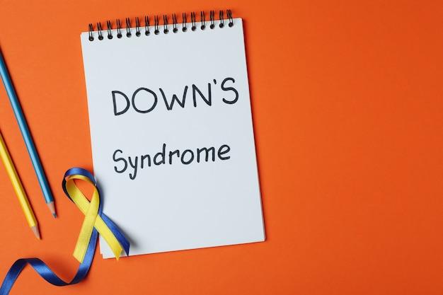 Texto síndrome de down, cintas de concienciación y lápices en naranja
