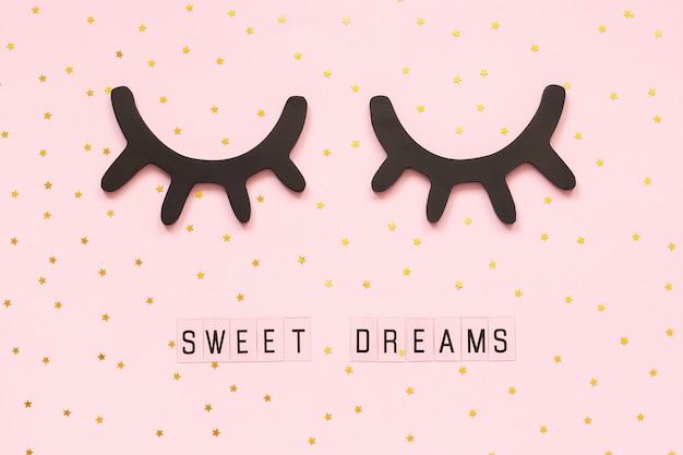 Texto sueños dulces y pestañas negras de madera decorativas, ojos cerrados estrella de oro sobre fondo rosa.