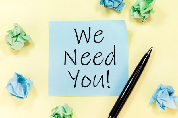 Texto te necesitamos en una etiqueta azul, bolígrafo negro y trozos de papel sobre fondo amarillo.
