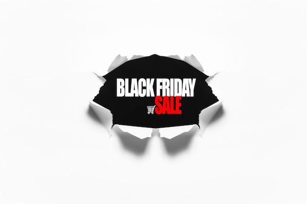 Texto de venta de viernes negro en agujero rasgado en la hoja de papel blanco.