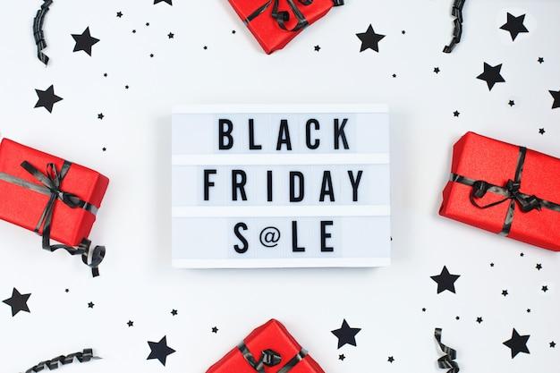 Texto de venta de viernes negro en caja de luz blanca y bolsas de regalo rojas, confeti