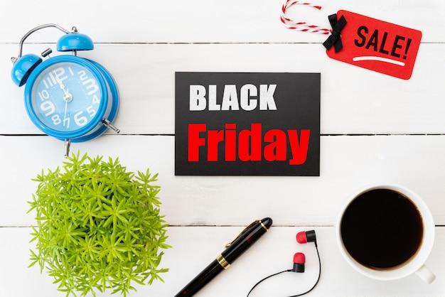 Texto de venta de viernes negro en etiqueta roja y negra con accesorios de oficina en mesa de madera blanca