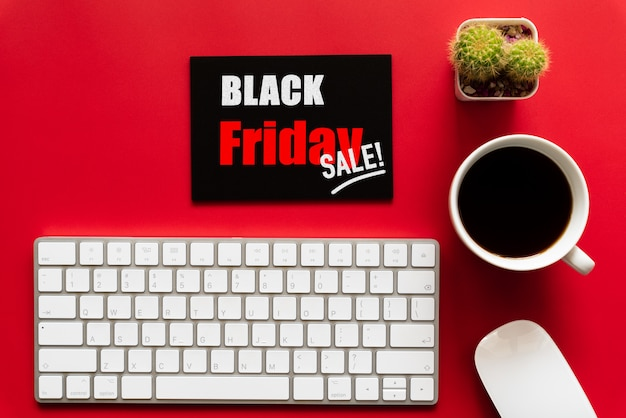 Texto de venta de viernes negro en una etiqueta roja y negra con taza de café, teclado sobre fondo rojo