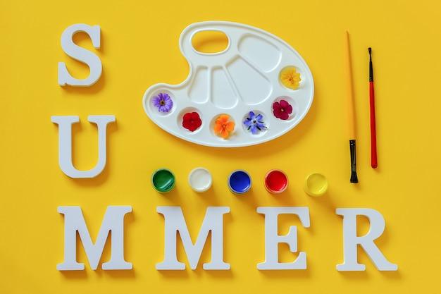 Texto de verano, flores de colores brillantes en la paleta artística, pincel y gouache. concepto creativo colores de verano