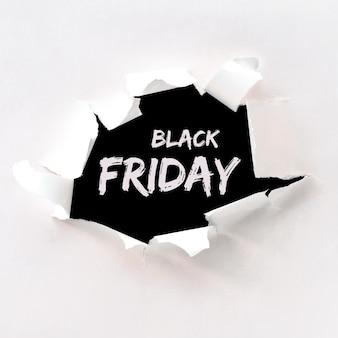 Texto de viernes negro en agujero de papel rasgado en papel blanco