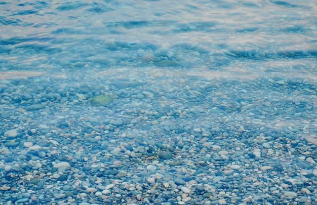 Textura de agua de mar cristalina transparente y guijarros, agua de mar de verano