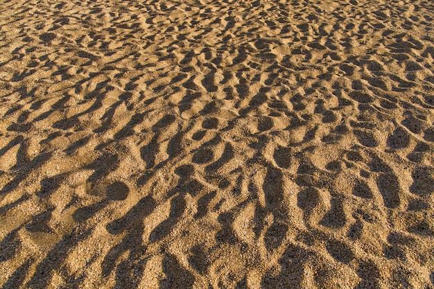 Textura de arena superficie irregular. sombras duras al mediodía en la arena.