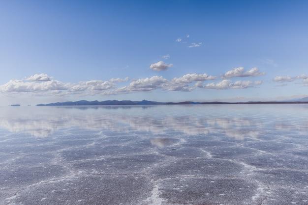 Textura de arena visible bajo el mar cristalino y el cielo