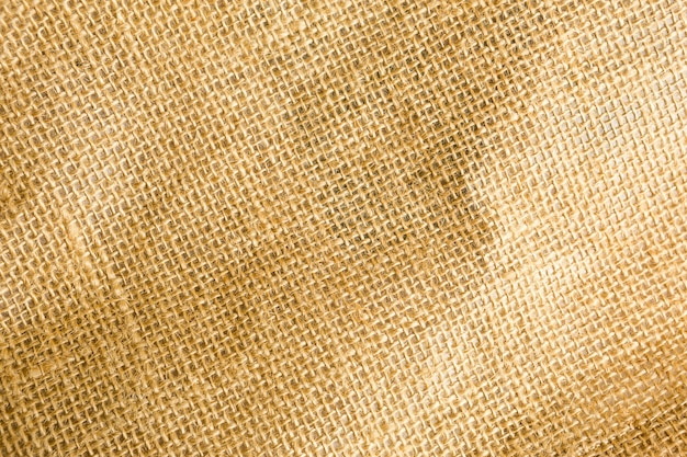 La textura de la arpillera, tejido áspero en una jaula de fibra natural, de color amarillo-marrón. copyspace, primer plano