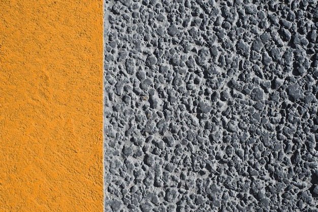 Textura de carretera con línea amarilla. carretera de asfalto granular oscuro y marcas de acera brillantes. fondo texturizado con espacio de copia