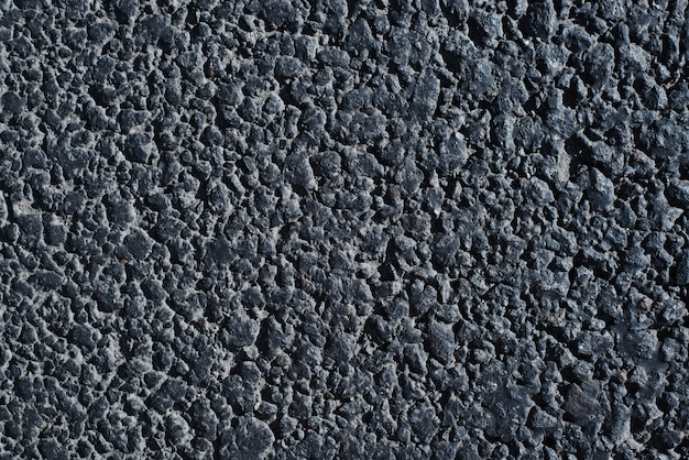 Textura de la carretera. primer plano de una carretera de asfalto oscuro al aire libre, vista superior. fondo de superficie granular rugosa.