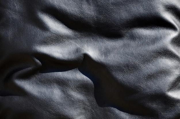 Textura de cuero negro o dermantin con pliegues.