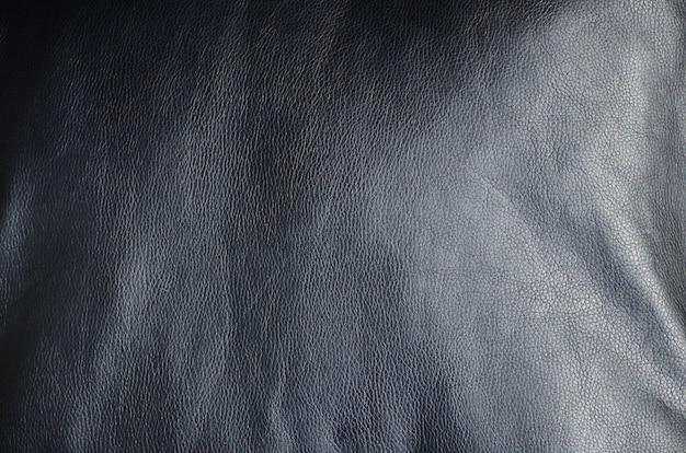 Textura de cuero negro o dermantina con pliegues, utilizada como material.