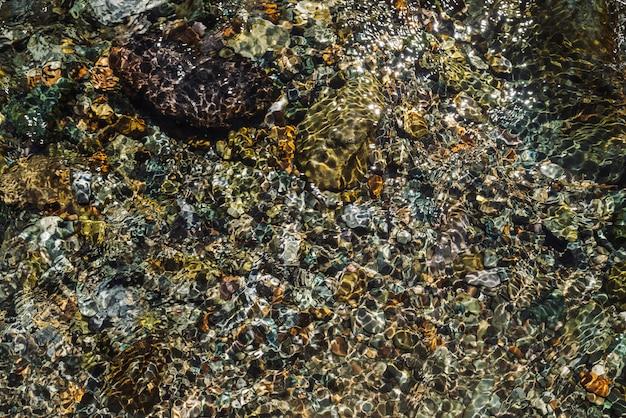 Textura detallada multicolor del fondo pedregoso del arroyo transparente de cerca. agua limpia en el arroyo de montaña. colorido de piedras lisas en la corriente del río con copyspace.
