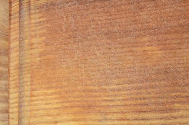 Textura detallada de la tabla de cortar de madera con muchas cicatrices del hacha y el cuchillo