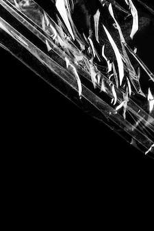 Textura de envoltura de plástico arrugada sobre un fondo negro
