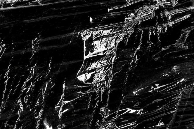 Textura de envoltura de plástico arrugada sobre un papel tapiz negro