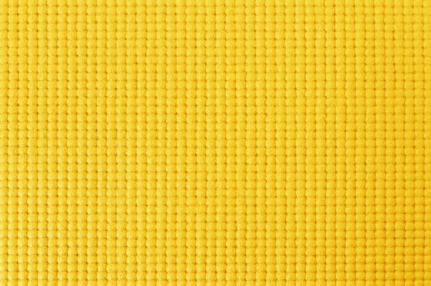 Textura de la estera de yoga de color amarillo para el fondo.
