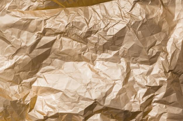 Textura de fondo abstracto dorado brillante hoja de metal arrugada.