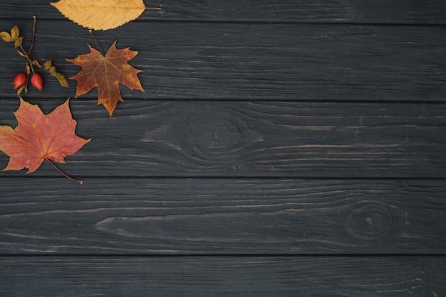 Textura de fondo con mesa de madera vieja y hojas otoñales amarillas. vista superior