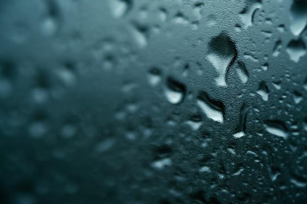 Textura de gotas grandes y pequeñas sobre el vidrio de la lluvia sobre fondo azul.