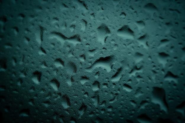 Textura de gotas grandes y pequeñas sobre el vidrio oscuro de la lluvia sobre fondo verde