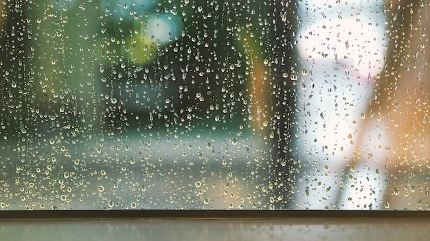 Textura de gotas de lluvia en el marco de la ventana de cristal de la sala de café y la naturaleza
