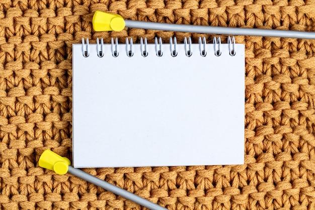 La textura de un hilo de punto amarillo y agujas de tejer. ropa de punto e invierno. copia espacio