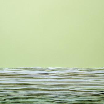 La textura de la imagen de fondo de la tela ondulada verde con pliegues paralelos o diagonales en papel con textura