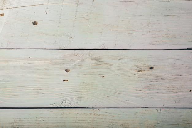 Textura de losa de madera clara con grietas y arañazos, fondo o papel tapiz.