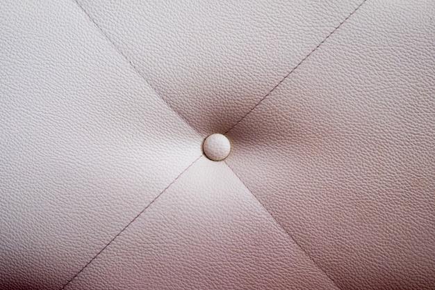 Textura de muebles de cuero blanco con botón.