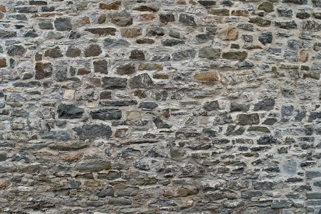 Textura de un muro de piedra. viejo fondo de la pared de piedra del castillo. muro de piedra salvaje. fondo natural