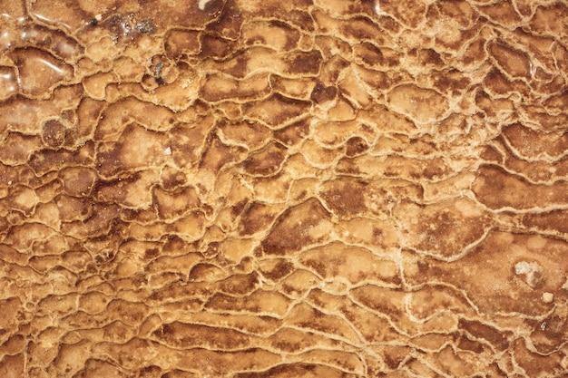 Textura naranja en un manantial mineral en las montañas, depósitos de piedra.