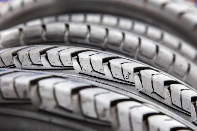 Textura de neumáticos negros en cierre del taller de reparaciones del coche para arriba.