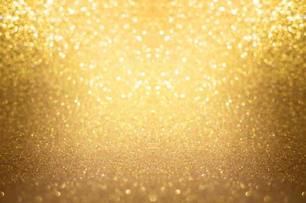 La textura del oro enciende el extracto del bokeh del fondo