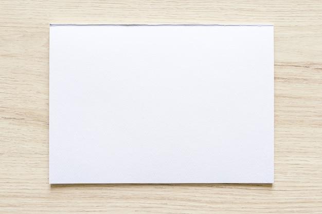 Textura de papel de acuarela sobre fondo de madera con trazado de recorte. hoja de papel blanco con bordes rasgados. papel de arte de textura de alta calidad en alta resolución.