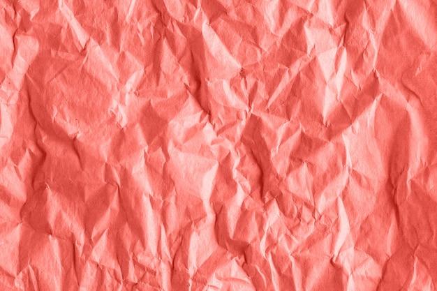 La textura del papel de embalaje áspero arrugado en el coral entonó, fondo abstracto