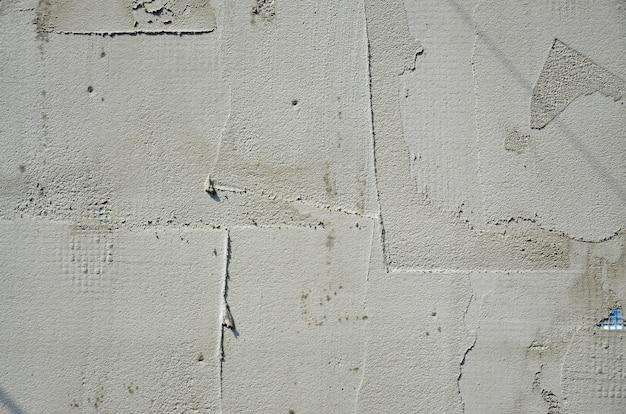 La textura de la pared, cubierta con placas de poliestireno de espuma gris, que están manchadas con una mezcla de refuerzo.