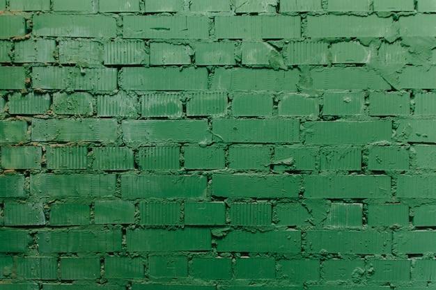 La textura de la pared de ladrillos de muchas filas de ladrillos pintados en color verde. fondo verde sucio de la pared de ladrillo del día del st patricks.