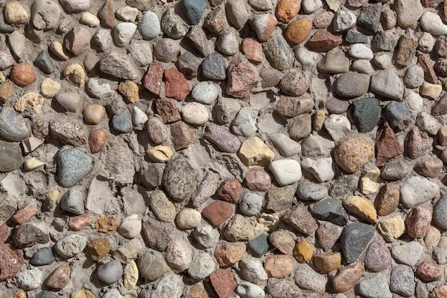 Textura de pared de piedra, camino de piedras redondas de tamaño pequeño y mediano