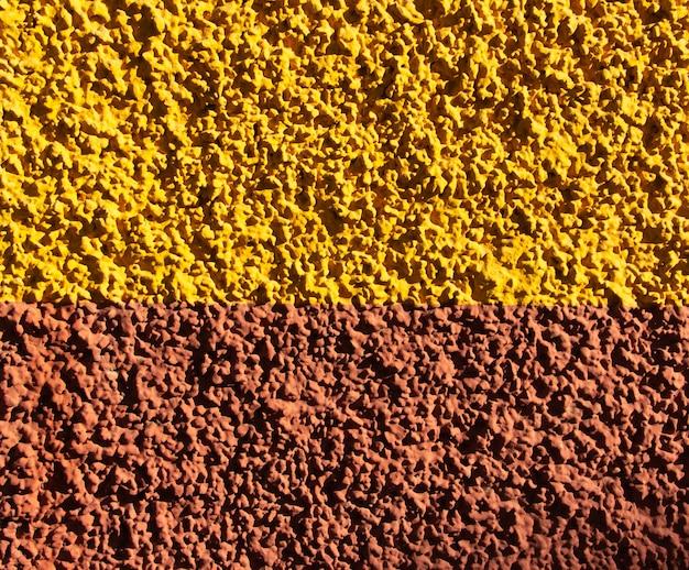 Textura de pared con pintura amarilla y naranja. muro de grano grueso. fondo.