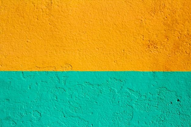 Textura de pared con pintura verde y naranja. fondo.