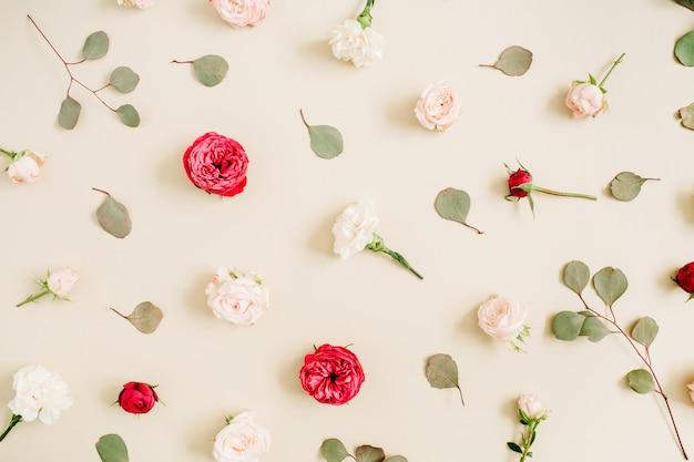 Textura de patrón de flores de rosas beige y rojas, hojas de eucalipto sobre fondo beige pastel pálido. endecha plana, vista superior