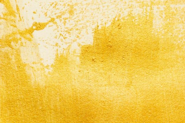 Textura de pintura acrílica dorada sobre papel blanco