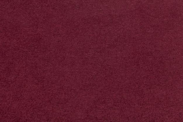 Textura del primer de papel rojo oscuro viejo. estructura de cartón denso. el fondo marrón.